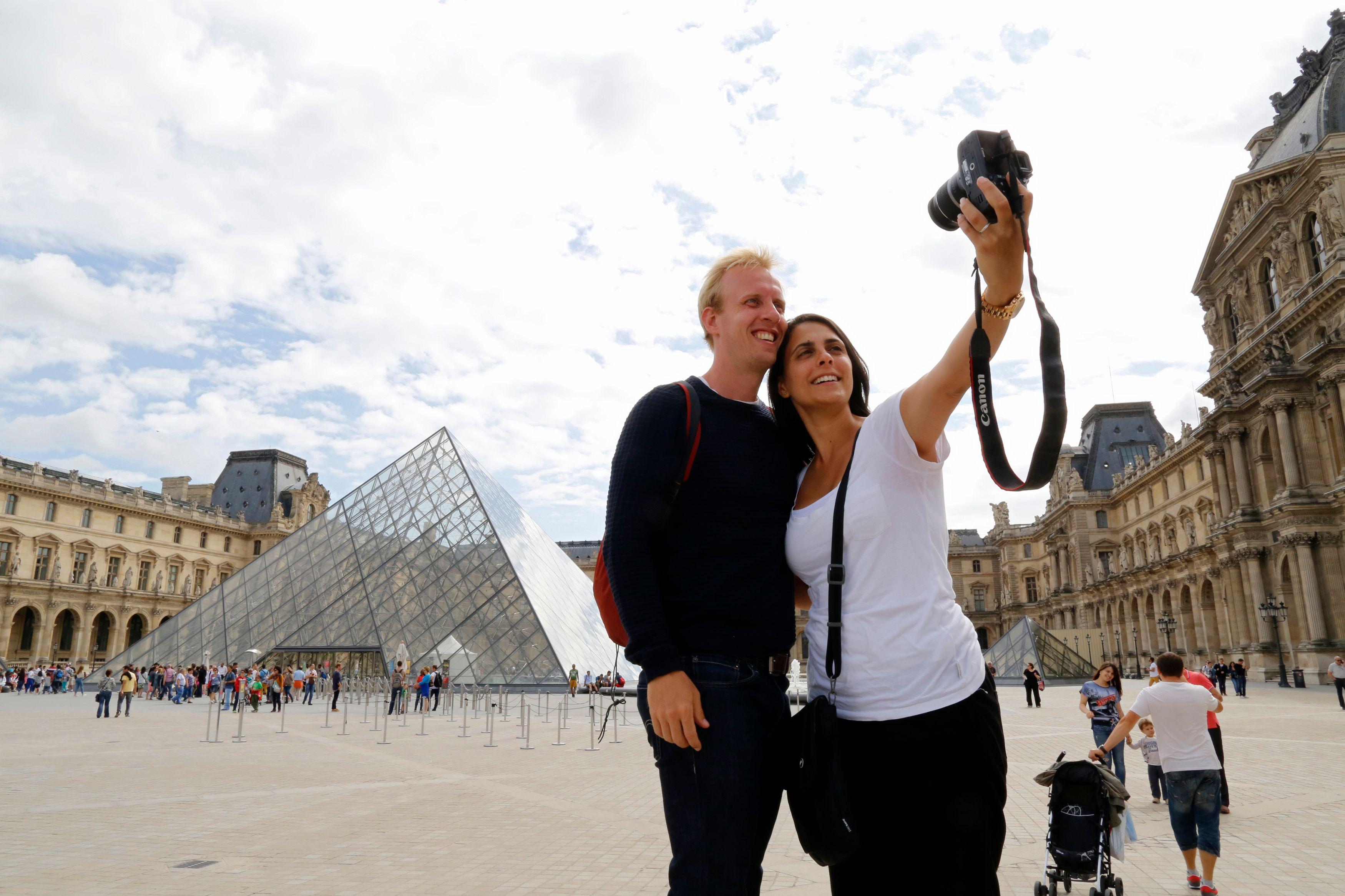 Des touristes se prennent en photo devant la pyramide du Louvre