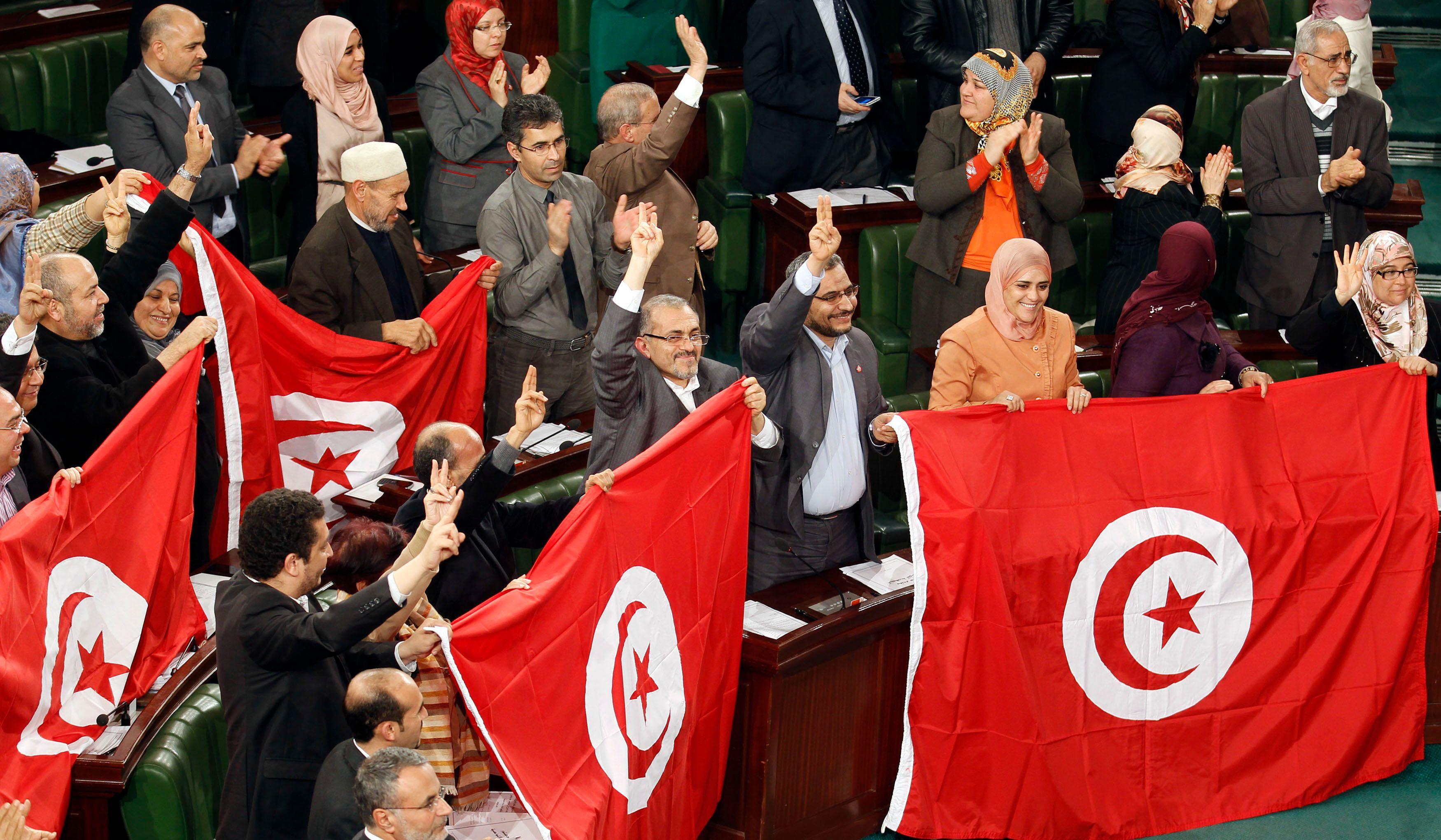 Des membres de l'Assemblée constituante saluent l'adoption par la Tunisie d'un nouvelle constitution, dimanche à Tunis.