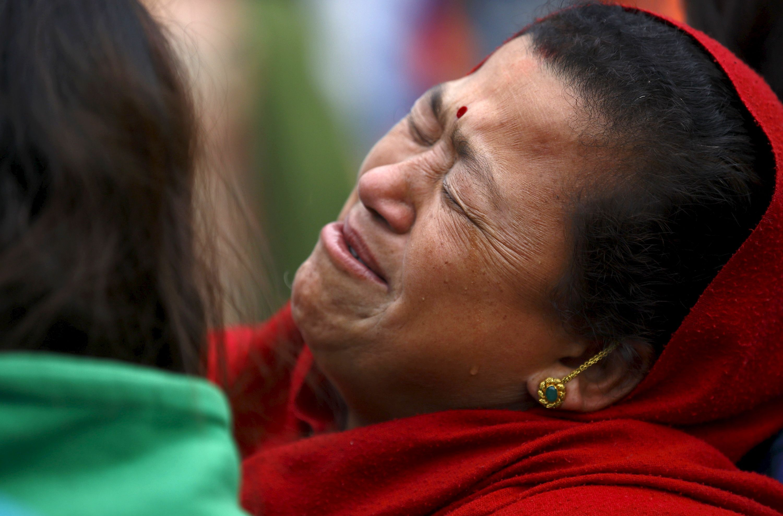 Une femme pleure la perte d'un être cher dans le tremblement de terre.