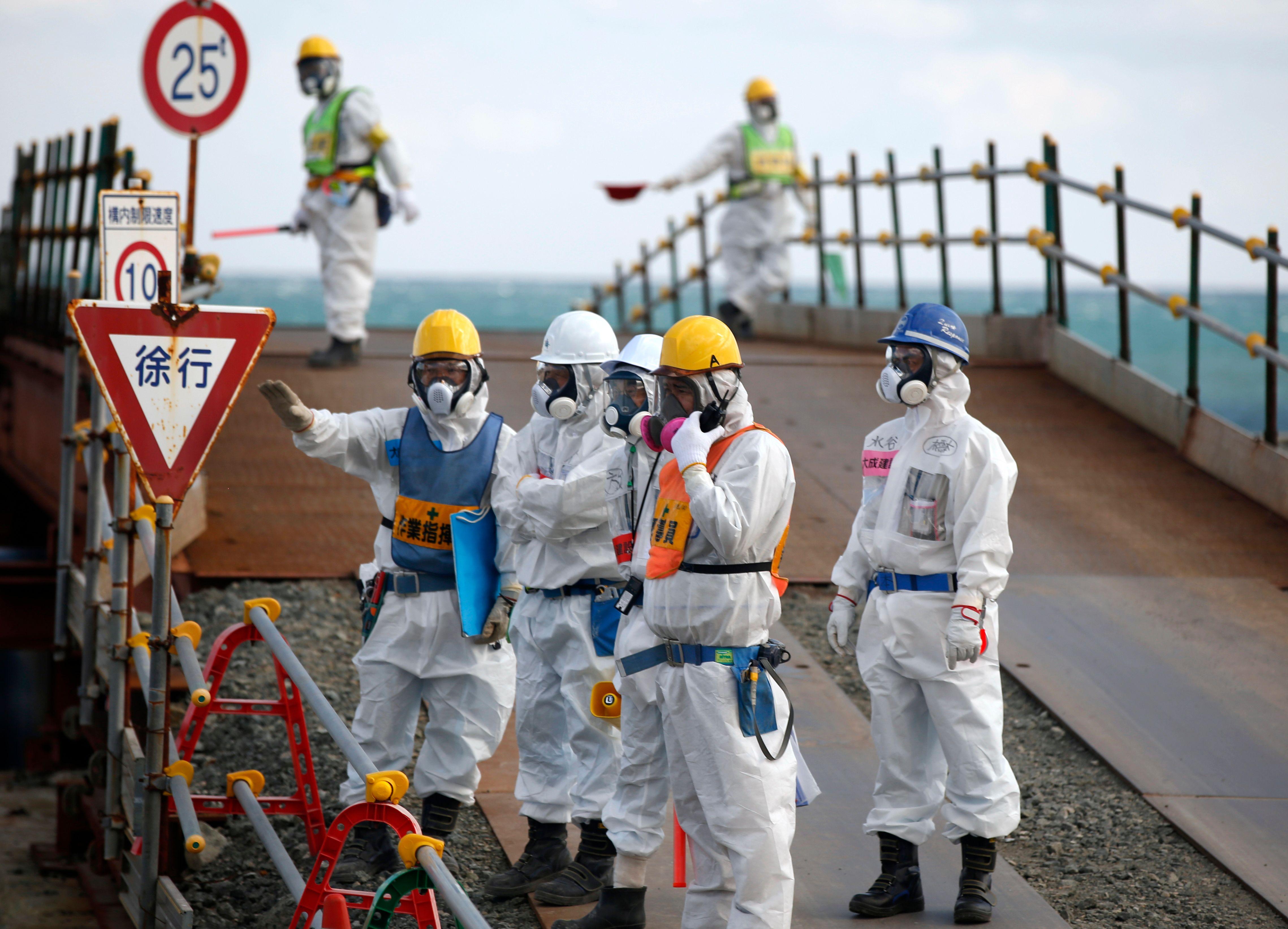 Cinq ans après la catastrophe, masque et combinaison de protection sont toujours de rigueur à Fukushima (Japon).