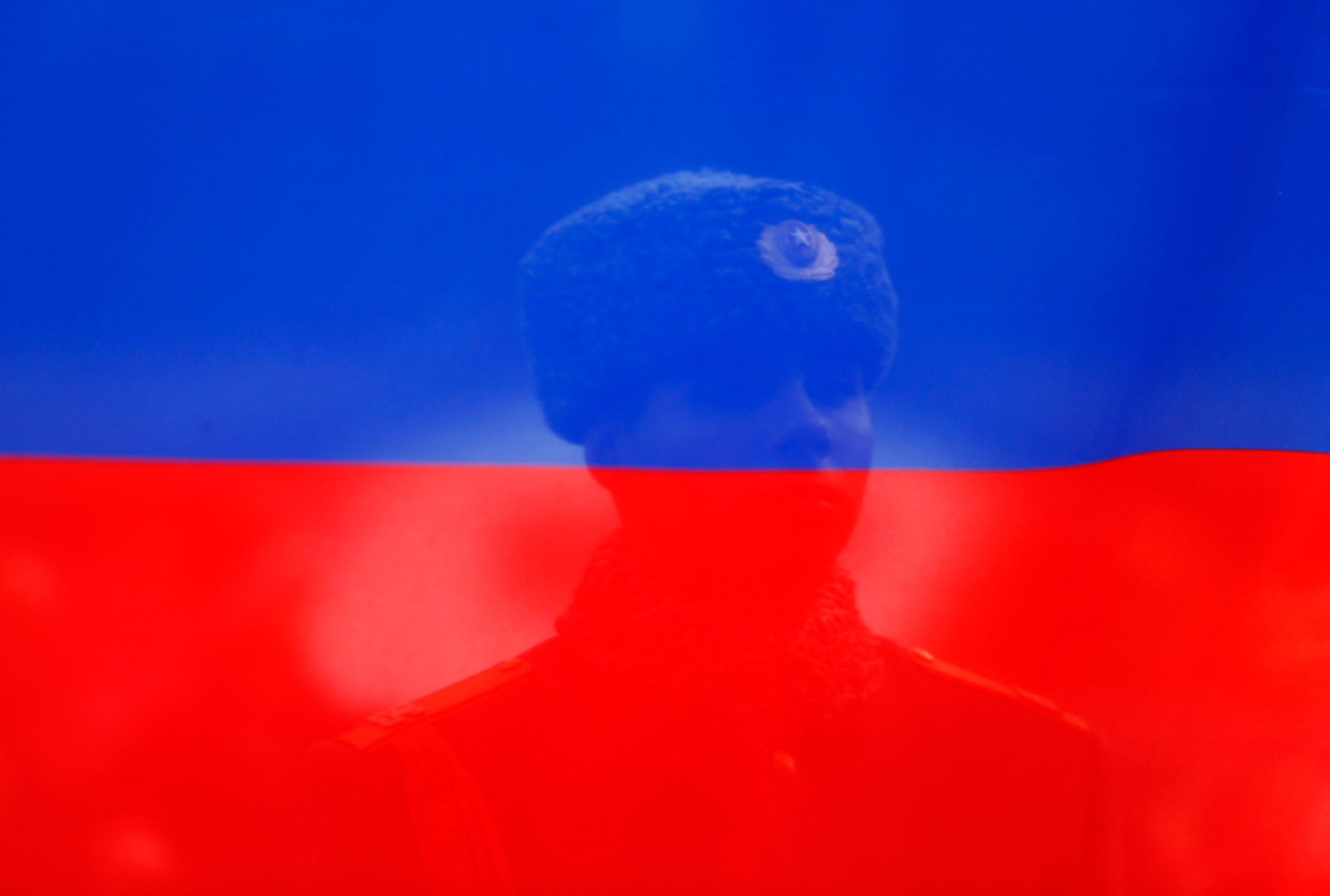Photo d'illustration / Le drapeau russe avec un soldat russe derrière.
