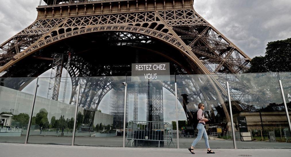 """Une femme passe devant la Tour Eiffel où un écran affiche le message """"Restez chez vous"""", le 24 avril 2020 à Paris, alors que le pays est en confinement face à la pandémie de Covid-19."""