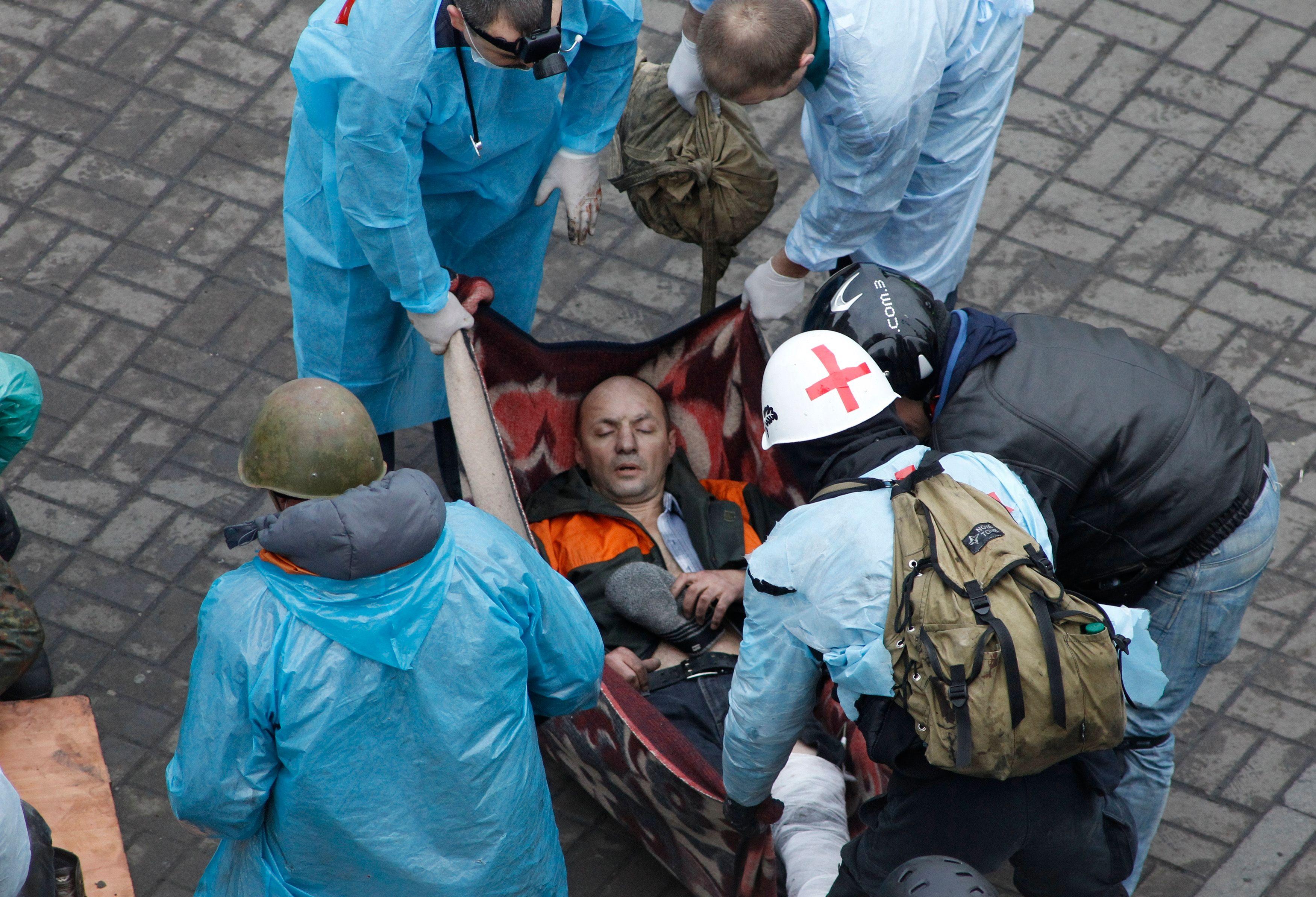 Un homme blessé reçoit des soins médicaux place de l'Indépendance à Kiev.